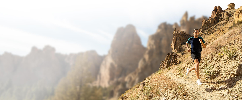 A runner runs along a desert trails wearing the Catamount trail shoe.