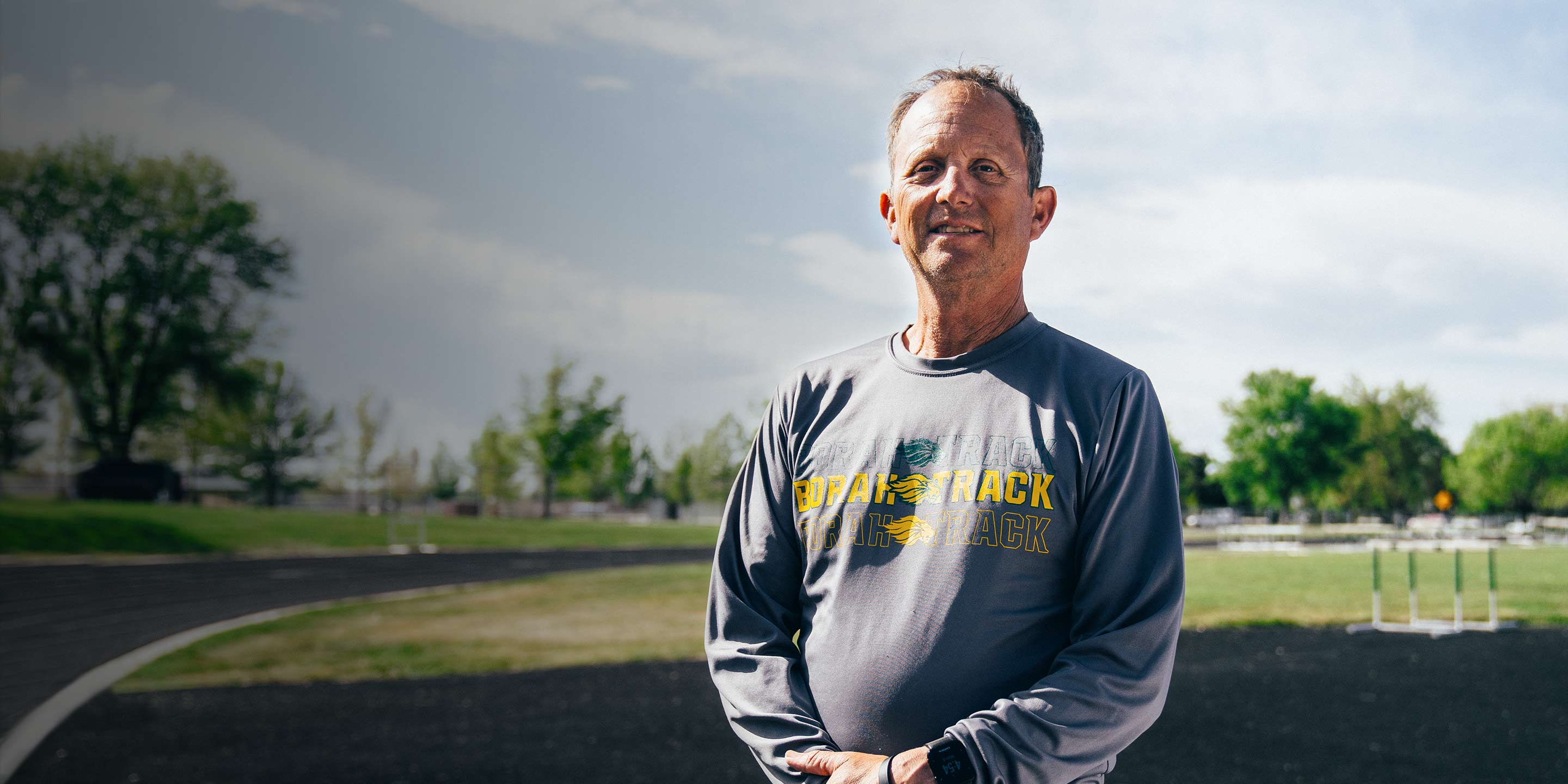The 2019 winner, Tim Severa, smiling at the camera in front of a track; the sun is out and his shirt reads Borah Track.