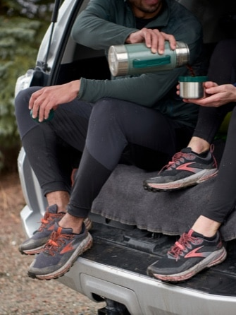 Two runners sitting in the trunk of a car while wearing the Cascadia 16 GTX