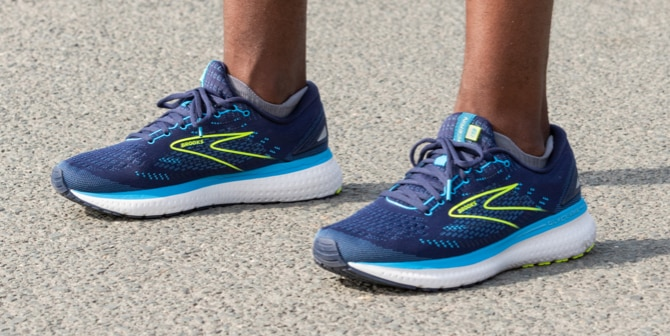 Close-up shot of the man standing in a pair of blue Brooks Glycerin 19 shoes.