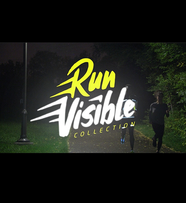Video still of a runner in the dark, wearing high-visibility gear with the text 'Run Visible Collection'