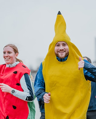 A man running in a banana dress next to a woman who is wearing a watermelon dress