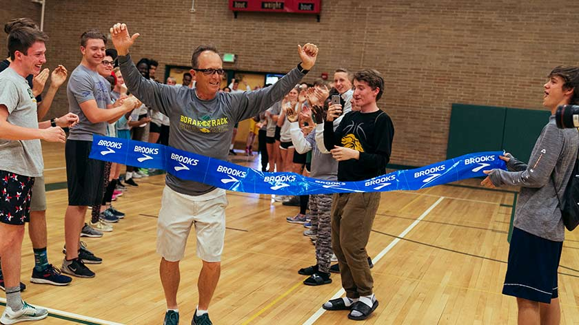 Tim Severa in a gym, celebrating as he crosses a finish line that reads 'Brooks'; there are students around him cheering