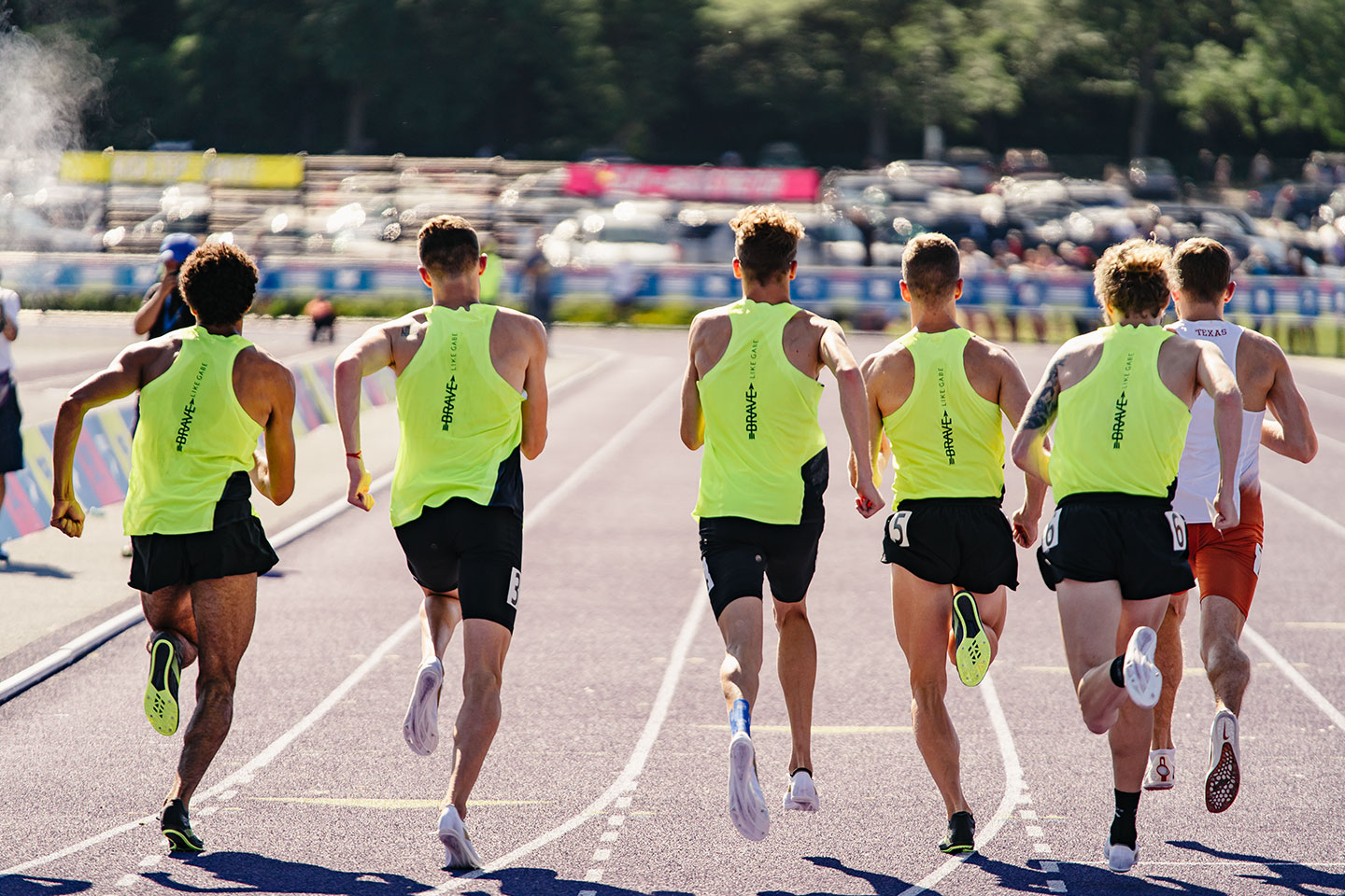 Athletes running on a track from behind in bright yellow uniforms