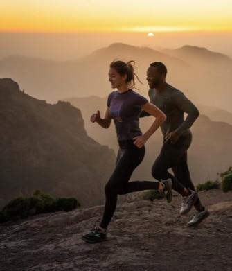 Two runners on a trail at sunrise