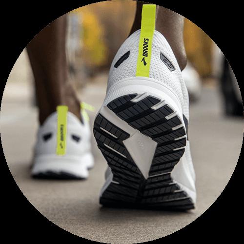 Runner wearing white and yellow revel 5's