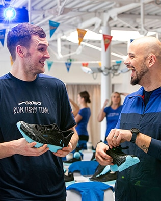Two men smiling at each other while holding the Brooks Hyperion Tempos