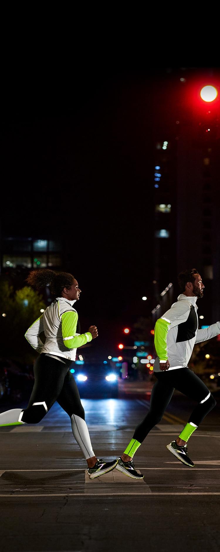 Visione laterale di un uomo e una donna che indossano la collezione Run Visible e attraversano una strada di notte