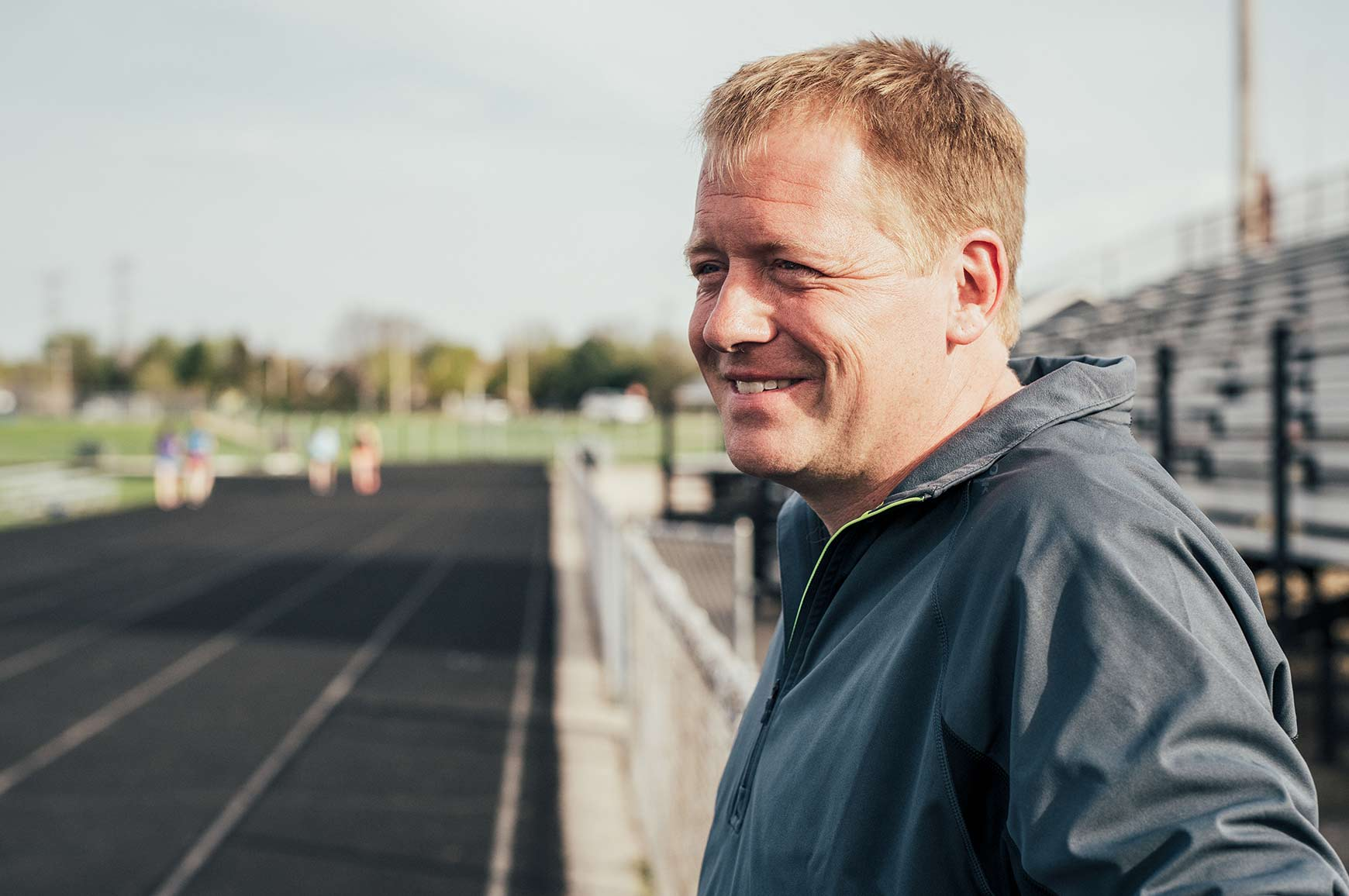 Mark Anderson from the side, smiling; behind him is a track