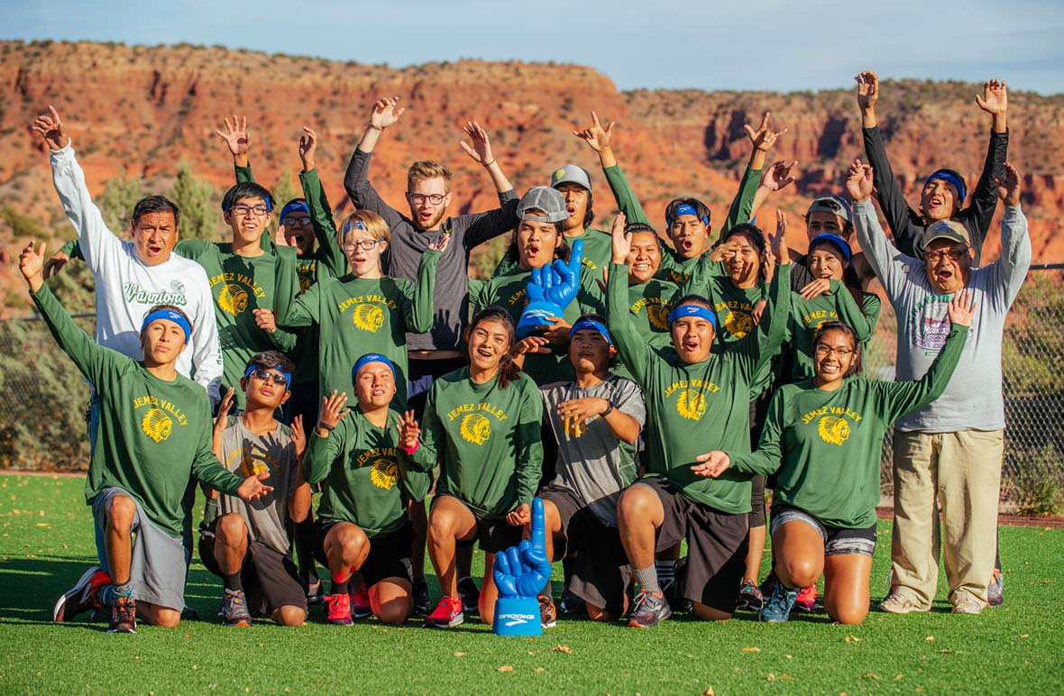 Jemez Valley school team taking a group picture and celebrating; the students and coaches are  cheering and have their arms in the air