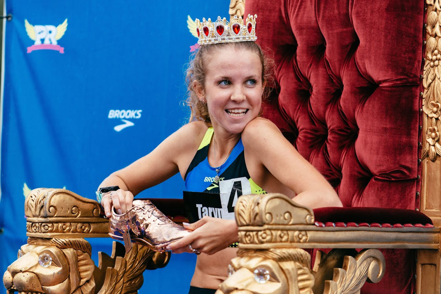 An athlete sits on a throne with a crown and holding a golden shoe