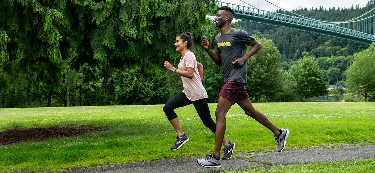 Female runner in a light pink running short, black tights and Brooks Running shoes and a male runner in a black shirt, maroon shorts and Brooks Running shoes running together in a park full of trees and grass with a blue bridge in the background.