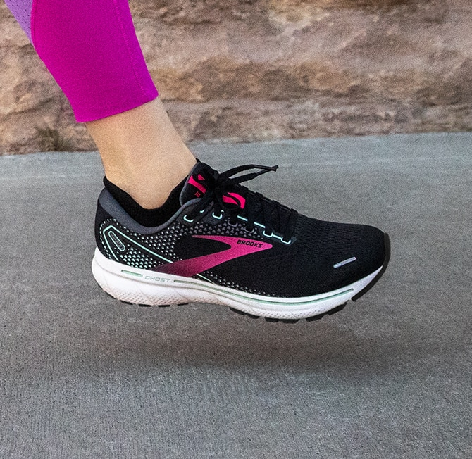 A close up of a black and pink running shoe