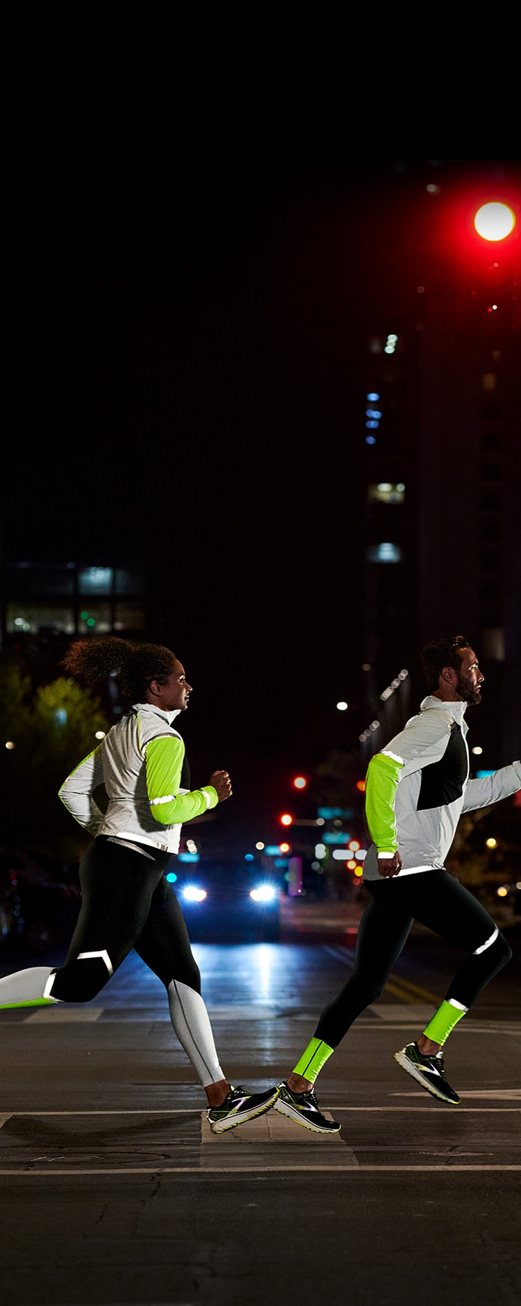 Side view of a man and a woman crossing a street at night while wearing the Run Visible collection