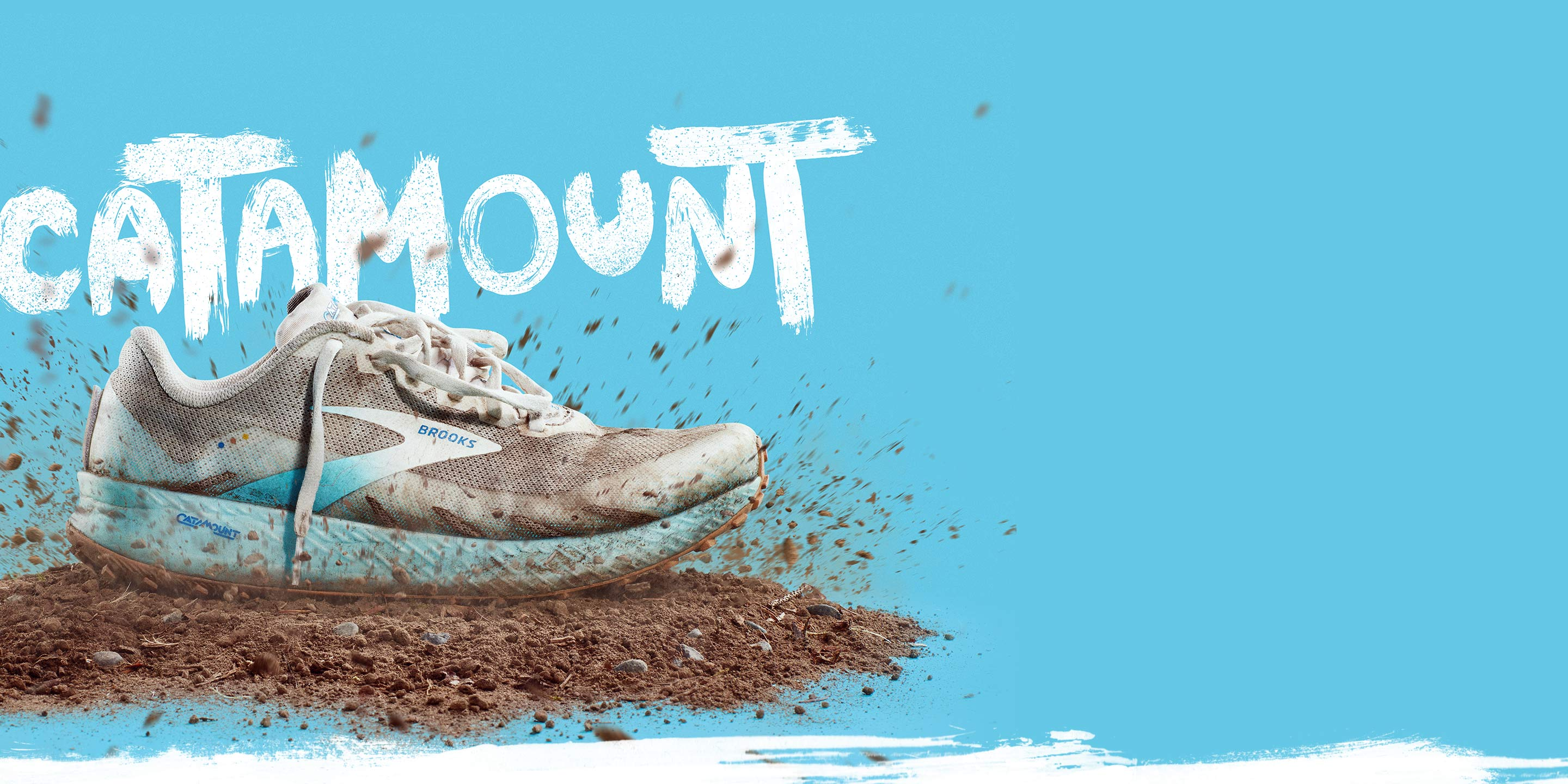 A trail shoe has just fallen on a mound of dirt, surrounded by dirt flying through the air.