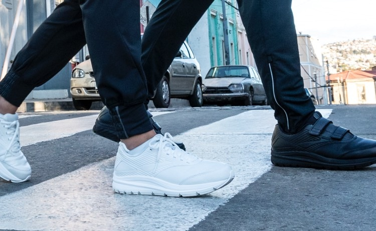 Two people wearing Addiction Walkers crossing the street