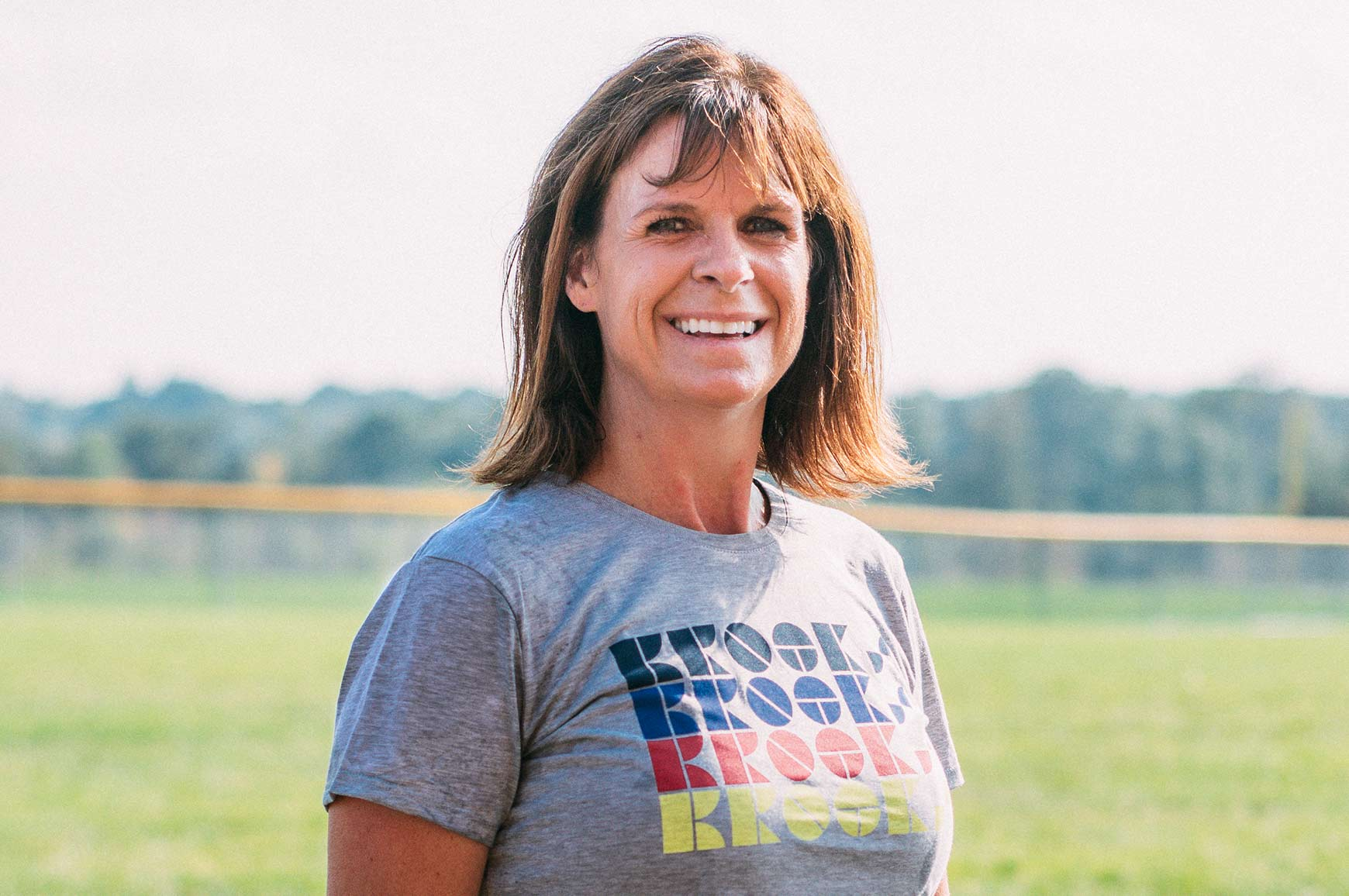 Denise Benson facing the camera and smiling; the background is of a field and the sun is out