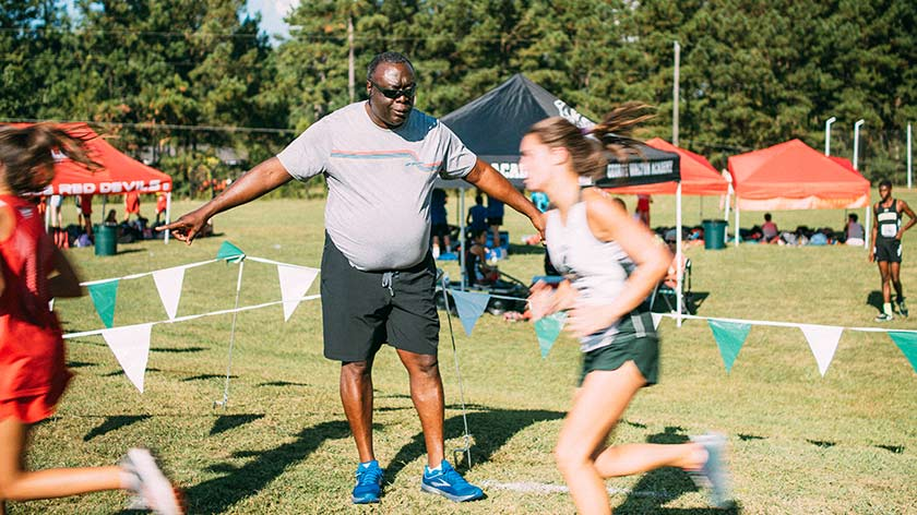 Nevill Anderson coaching his athletes as they run by during an event; the sun is out and there are tents and athletes in the background