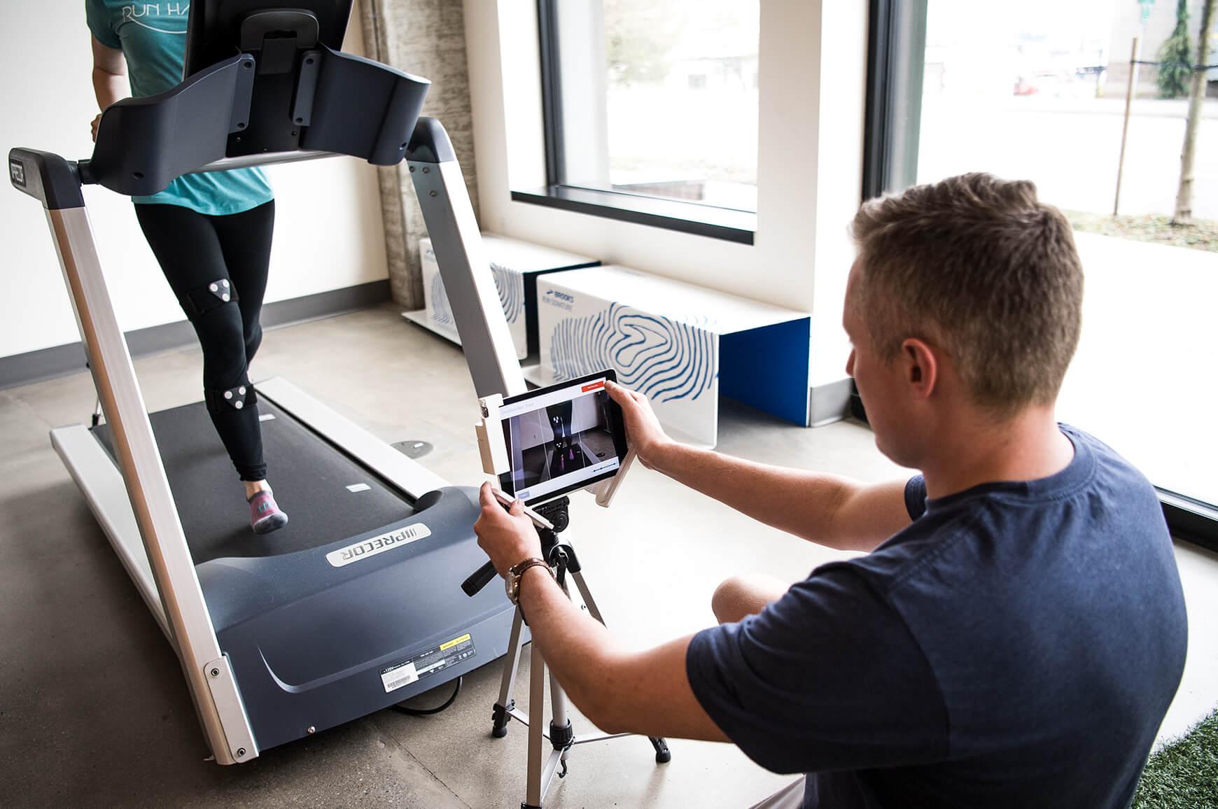 A Brooks employee analyzing a runner's gait on a treadmill