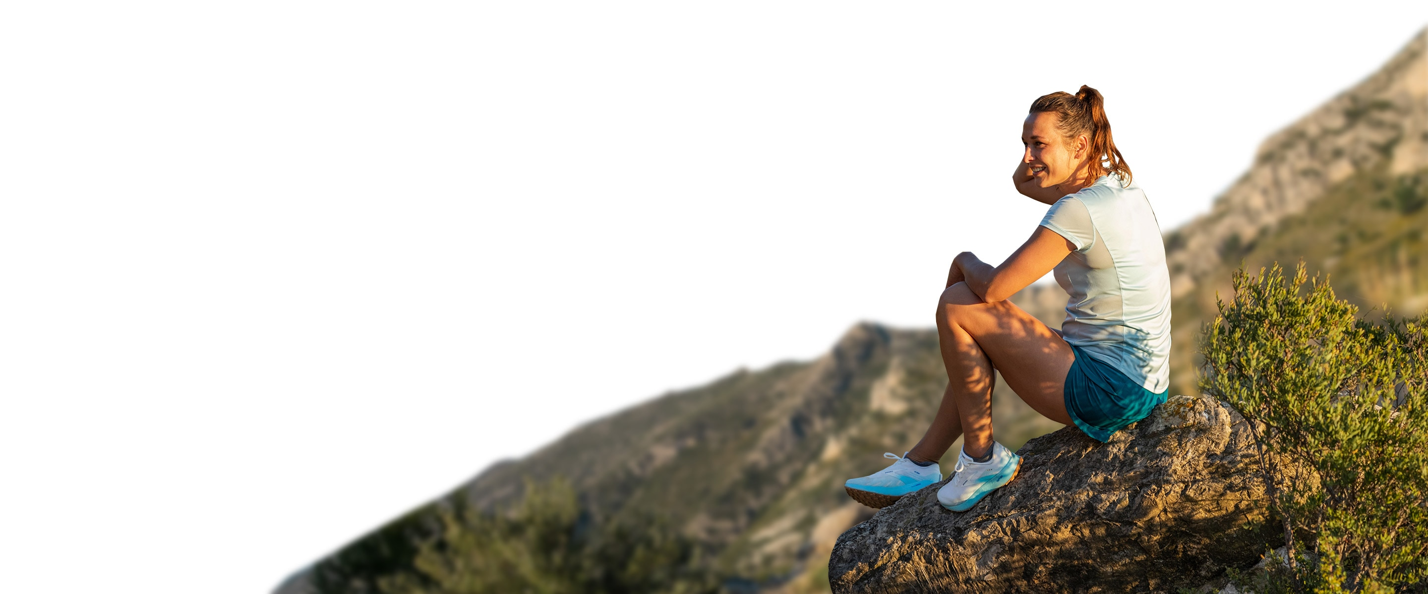 A runner sits atop a mountain in the Catamount
