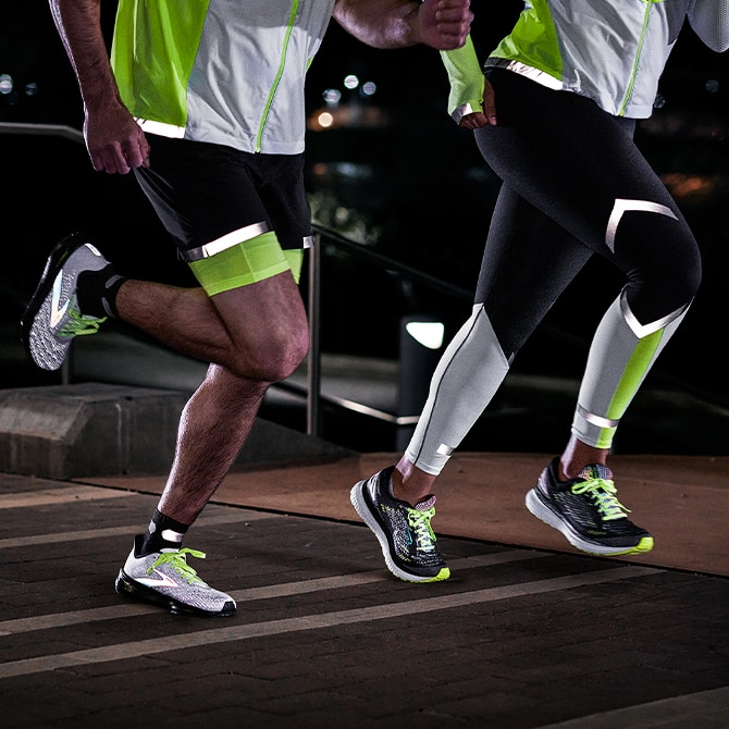 Two runners running in the dark and wearing the Brooks Run Visible Collection
