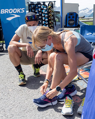 A woman lacing up a pair of Brooks