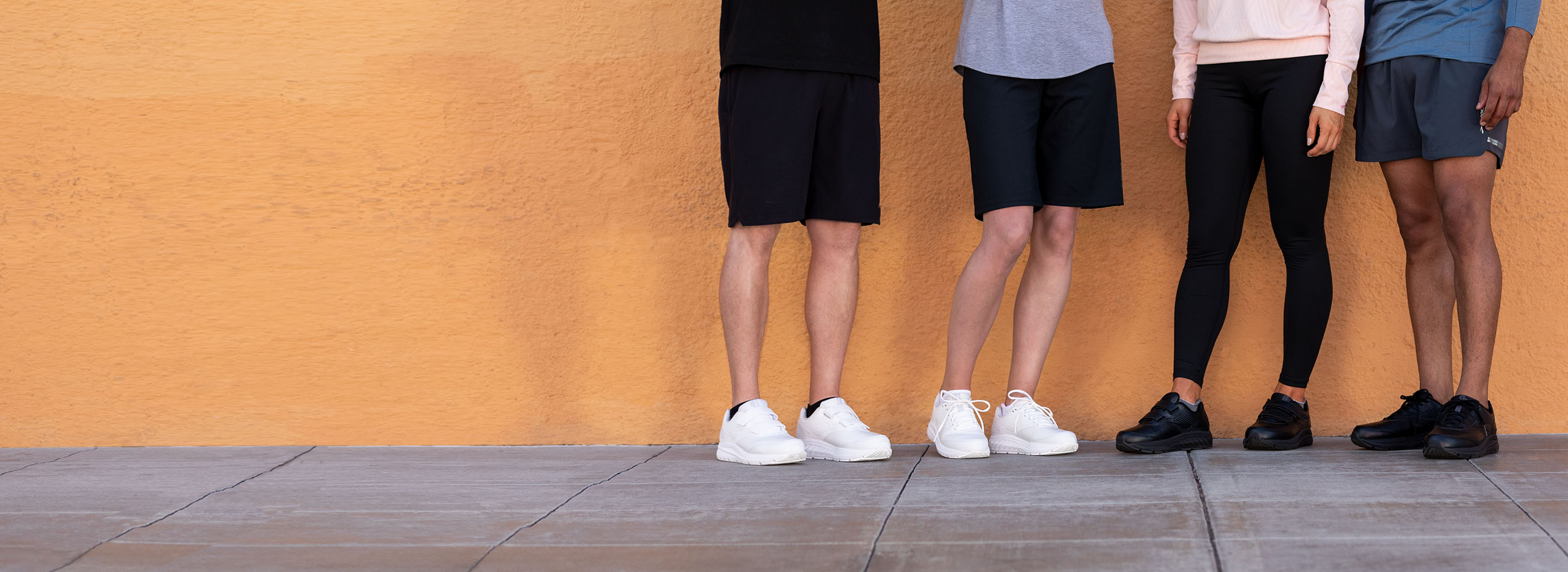 A picture of four people from the waist down wearing the Addiction Walker 2 and Addiction Walker 2 V-Strap; they are standing in front of a bright orange wall