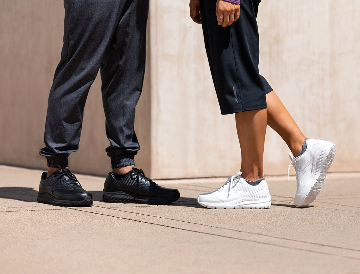A picture of two people from the waist down; they are both wearing the Addiction Walker 2, one in black and one in white