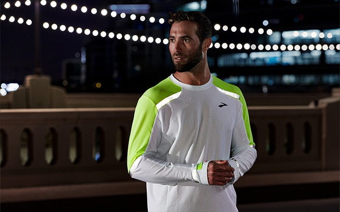 A runner in the dark wearing the Brooks Run Visible collection