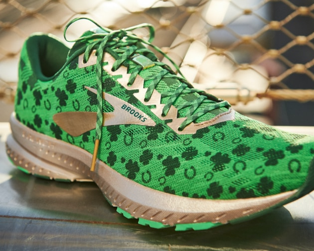 A green shoe with shamrocks and a gold sole