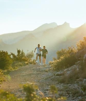 dos personas corriendo por una colina
