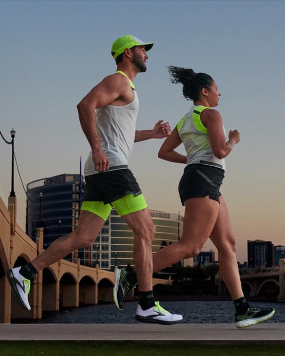 Visione laterale di una donna e un uomo che corrono