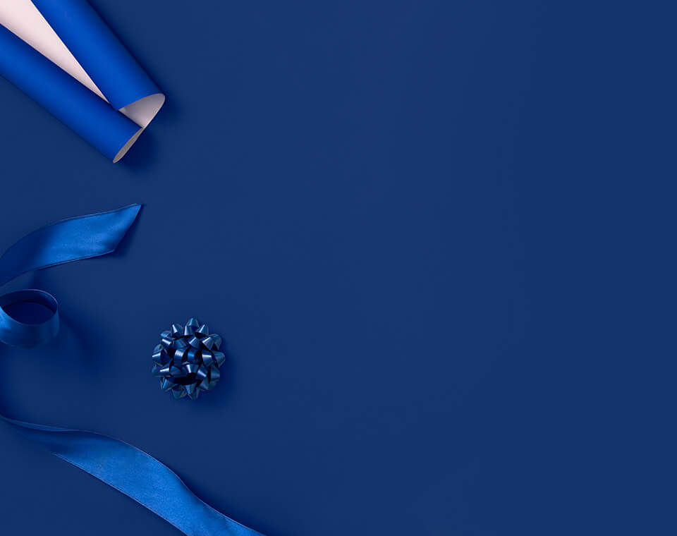Blue and white rolled wrapping paper, gift ribbons, and blue ribbons on a blue background.