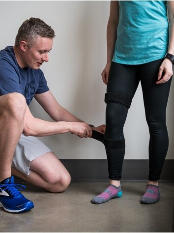 Man putting a knee monitor on a woman