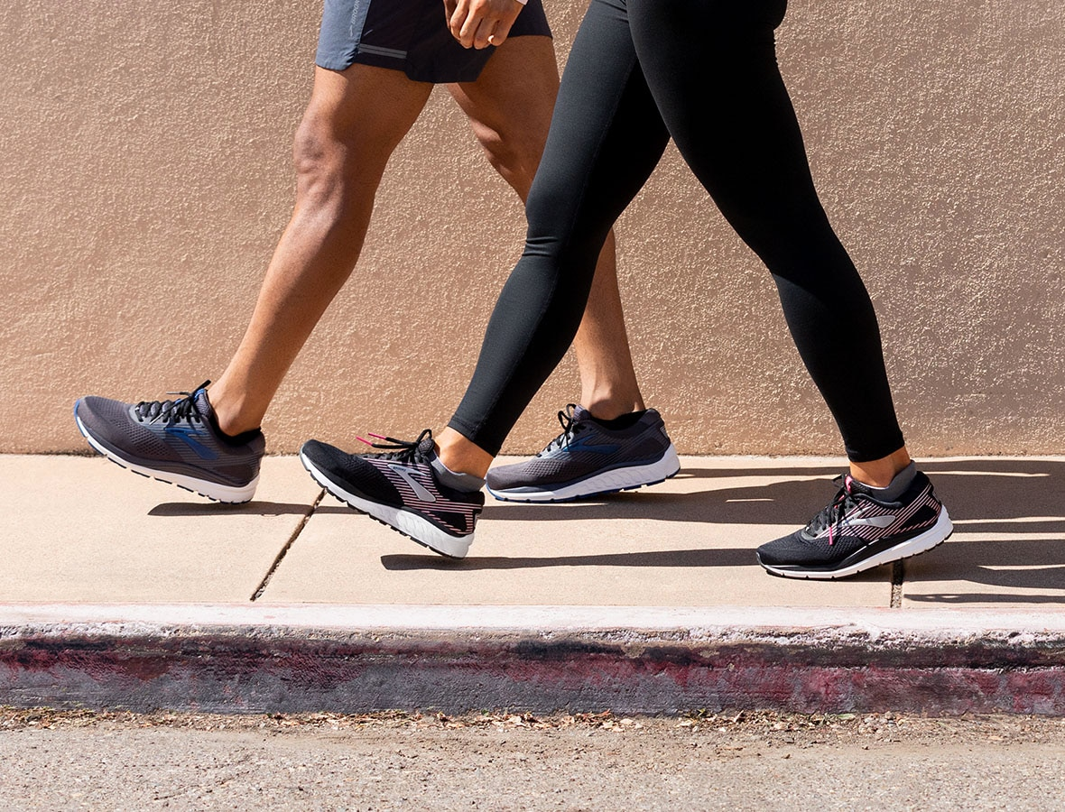 A picture of two people from the waist down walking on a sidewalk; they are both wearing the Addiction 14 in black