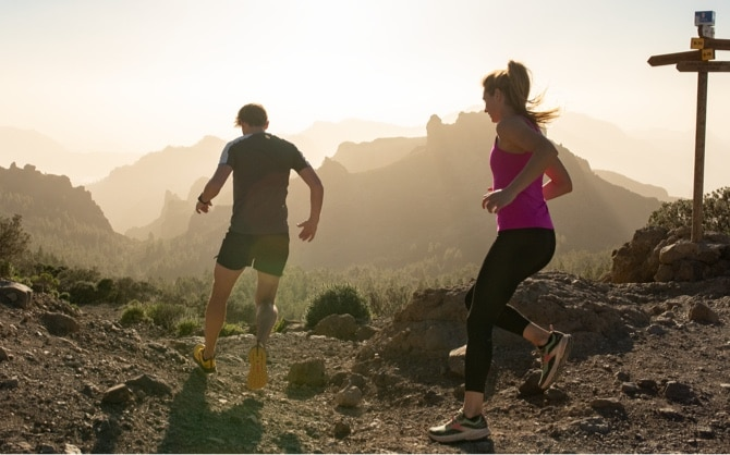 Two runners running on a trail in the mountains