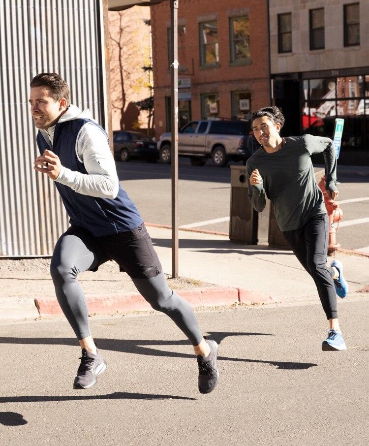 Runners midstride running on a sidewalk